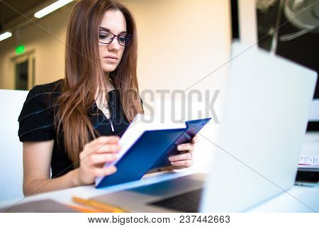 Young Woman University Student Reading Information From Textbook, Sitting With Laptop Computer In Mo