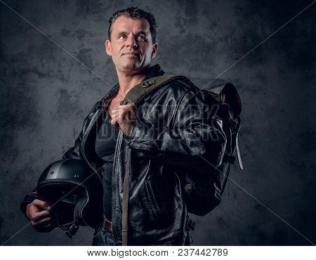 Portrait Of Middle Age Biker In Sports Jacket, Holds Motorcycle Helmet On Grey Background.