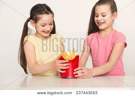Happy Little Girls Holding A Bag Of Fries Isolated On White Background. Fast Food Against Healthy Fo