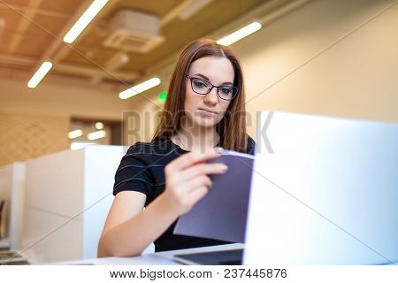 Intelligent Woman Entrepreneur Reading Information From Notebook, Sitting With Laptop Computer In Of
