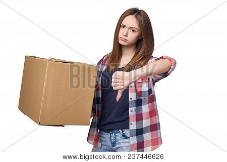 Delivery, Relocation And Unpacking. Discontent Young Woman Holding Cardboard Box And Gesturing Thumb