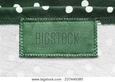 Blank Green Clothes Label On White And Green Textile Background Closeup