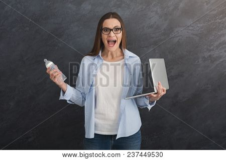 Angry Businesswoman Holding Laptop And Baby Bottle On Grey Background. Young Working Mother Has No T
