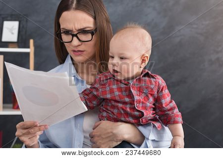 Serious Business Mom Working With Documents In Office While Spending Time With Her Cute Baby. Busine