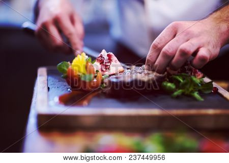 closeup of Chef hands in hotel or restaurant kitchen serving beef steak with vegetable decoration