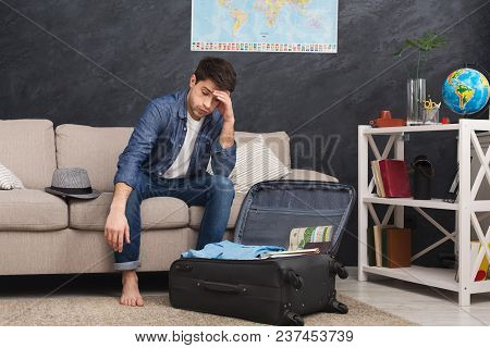 Tired Man Packing Suitcase For Trip