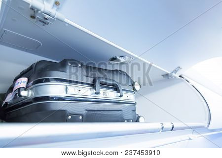 Luggage Shelf With Luggage Suitcase In An Airplane. Aircraft Interior. Travel Concept