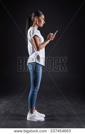 Online Age. Cheerful Positive Attractive Woman Standing And Holding Her Smartphone While Using Socia