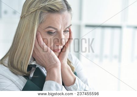 Close Up Portrait Of Upset Mature Woman In Office