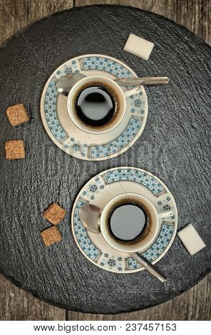 Drinks, drinking, energy and caffeine concept-two cups of coffee on a dark slate stand and wooden background. poster