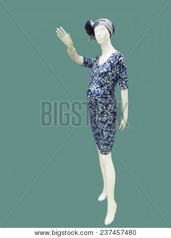 Full-length Female Mannequin Dressed In Clothes For Pregnant Women Against Green Background. No Bran