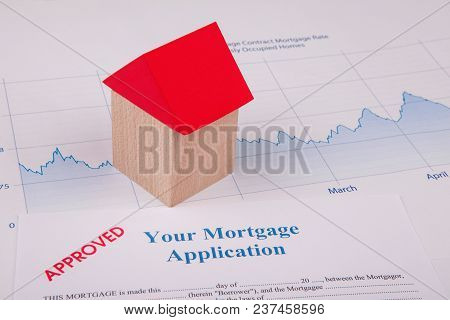 Business Balance Approved Mortgage Application On Desk