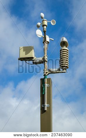 Weather Station On A Pole With A Cloudy Blue Sky.
