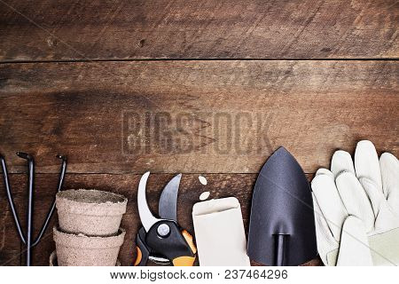 Background Of Various Gardening Tools, Gloves And Vegetable Seeds Shot From Above Over A Rustic Wood