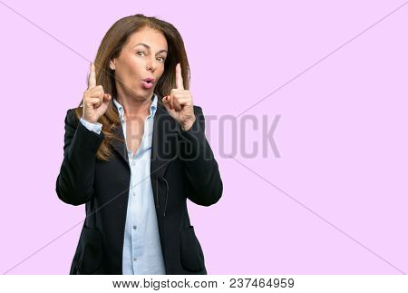 Middle age business woman happy and surprised cheering expressing wow gesture pointing up