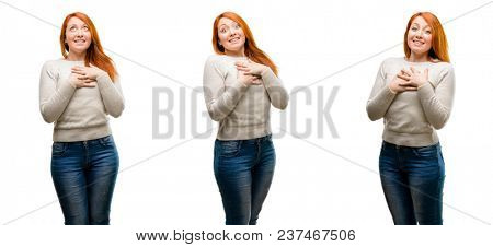 Young Beautiful redhead woman having charming smile holding hands on heart wanting to show love and sympathy