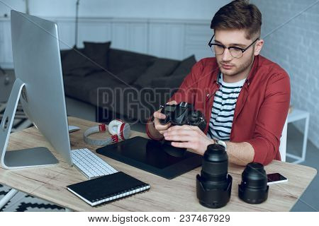 Man Freelancer With Camera In Hands At Work By Table With Computer And Graphic Tablet