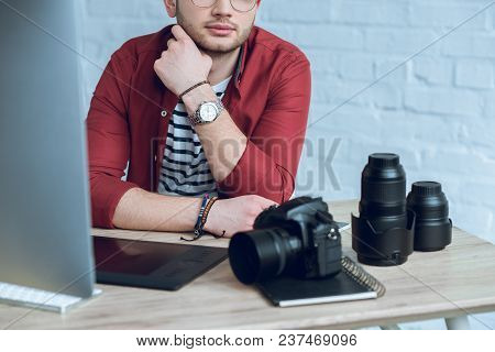 Bearded Man Sitting By Table With Camera And Graphic Tablet