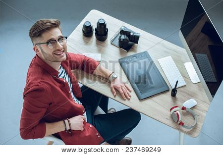 Young Photographer Sitting By Table With Camera And Graphic Tablet
