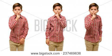 Handsome toddler child with green eyes with index finger on lips, ask to be quiet. Silence and secret concept