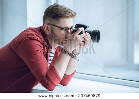 Young Photographer Shooting With Digital Camera By Light Window