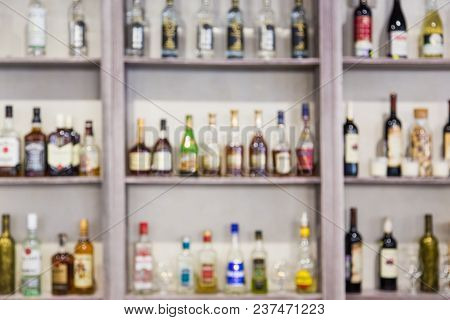Blurred Background From Bottles With Alcohol On The Shelves In The Bar
