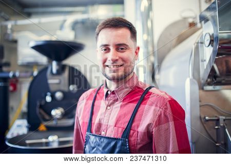 Portrait of young man in apron on background of industrial coffee grinder