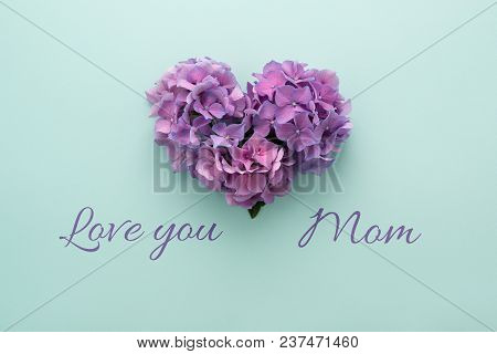 Text Love You Mom & Heart Shape Made Of Violet Flowers On Blue