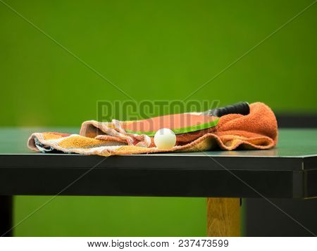 table tennis racket with towel on a table - focus at the racket/blade and ball