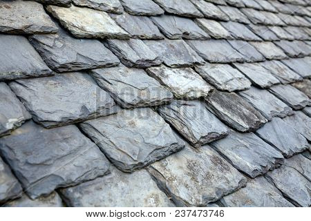 Aged weathered grey slate tile roof in Scotland UK