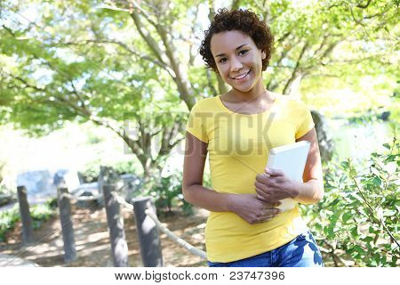 A pretty african american woman with a book at the park