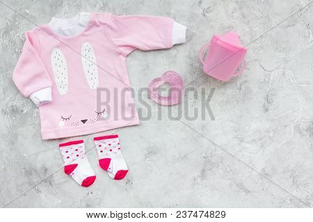 Newborn Baby's Background. Clothes For Small Girl With Booties On Grey Background Top View Copy Spac