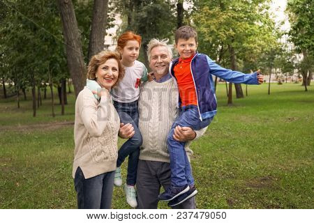 Happy senior couple and their grandchildren in park