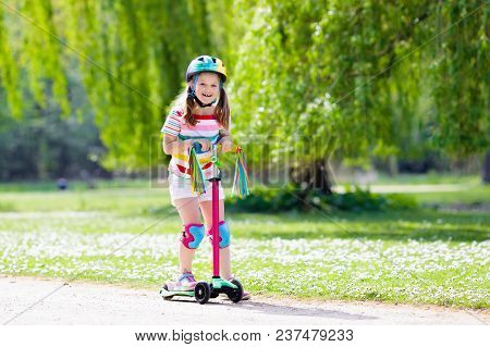 Child Riding Kick Scooter In Summer Park.