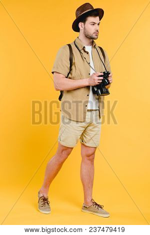 Full Length View Of Young Man In Shorts And Hat Holding Camera And Looking Away Isolated On Yellow