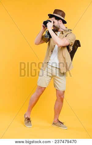 Full Length View Of Smiling Young Man In Shorts And Hat Photographing With Camera Isolated On Yellow