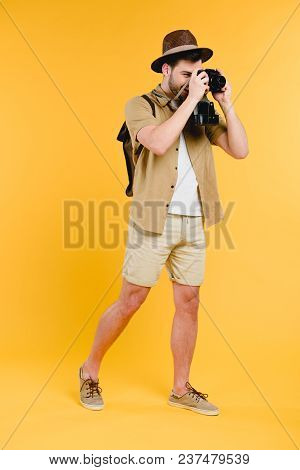 Full Length View Of Young Male Traveler Photographing With Camera Isolated On Yellow