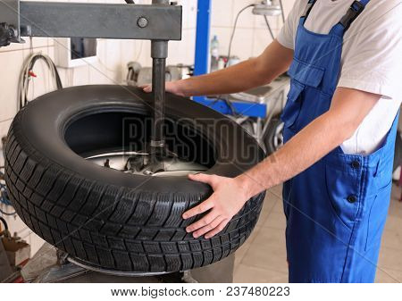 Mechanic changing car tire in service center