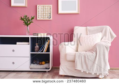 Elegant room interior with comfortable armchair near color wall
