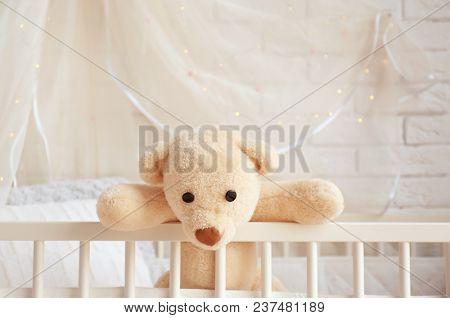 Cute toy bear in crib