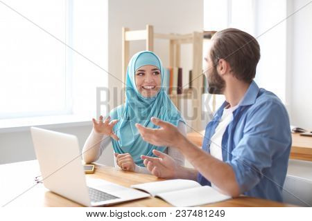 Male student and his Muslim classmate using laptop in library