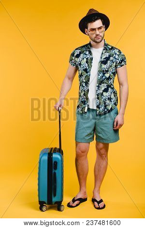 Full Length View Of Handsome Young Man In Summer Outfit Holding Suitcase Isolated On Yellow