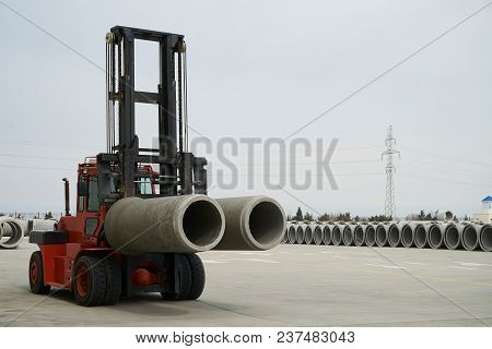 Heavy Forklift Loader For Warehouse Works Outdoors With Concrete Pipes. Industrial Production Of Cem