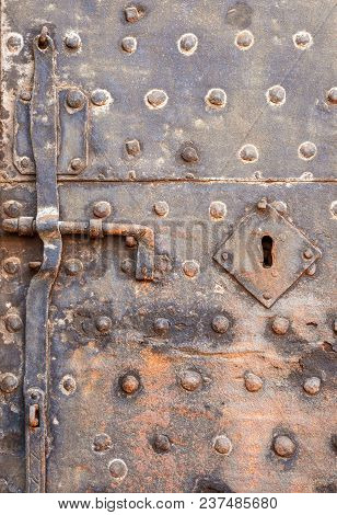 Very Old Iron Door, Lock, Damaged Keyhole And Studs With Rust