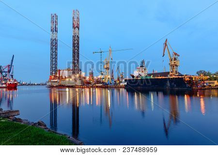 Oil Rig Docked In Shipyard Of Gdansk In Dusk. Poland