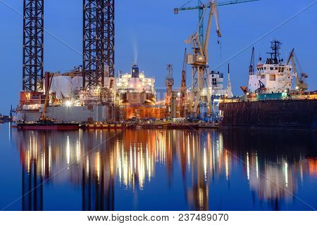 Oil Rig Docked In Shipyard Of Gdansk At Night. Poland