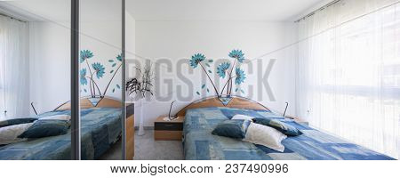 Very bright bedroom, colorful blankets and large pillows. Nobody inside