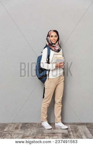 Full length portrait of a happy young arabian woman student with backpack holding books isolated over gray background