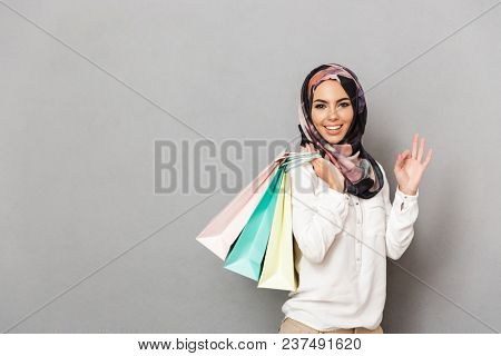 Portrait of a happy young arabian woman carrying shopping bags and showing ok gesture isolated over gray background