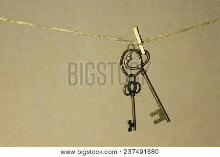Vintage Key Hanging On A Rope On A Gold Background